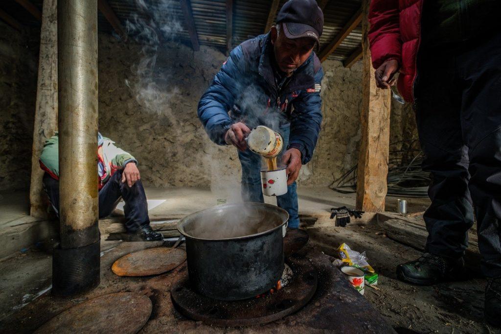 man pouring chai tea